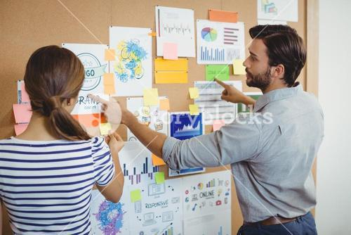 Male and female executives discussing over bulletin board