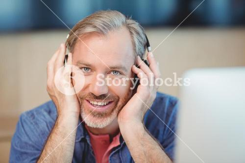 Male graphic designer listening music on headphones
