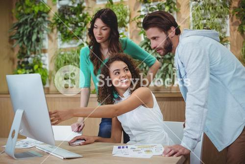 Team of graphic designers discussing over computer at desk