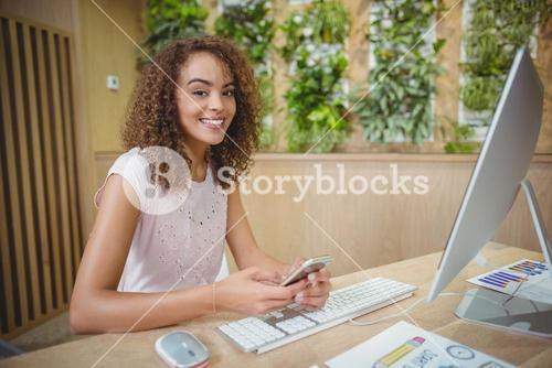 Portrait of female executive sitting at desk and using mobile phone