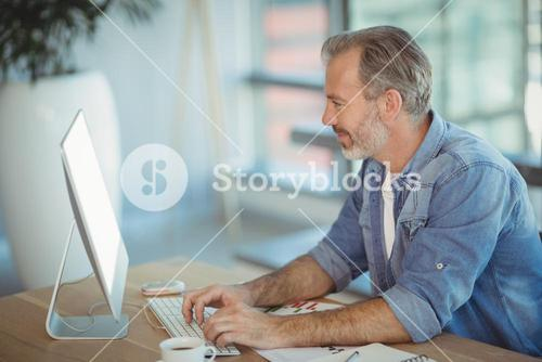 Male executive sitting at desk and working on personal computer