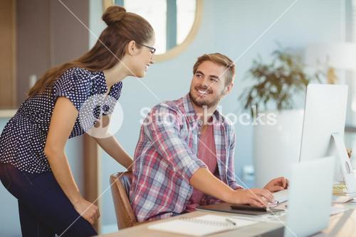 Graphic designers interacting while working on personal computer