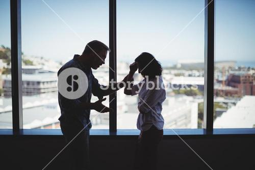Couple arguing near the window