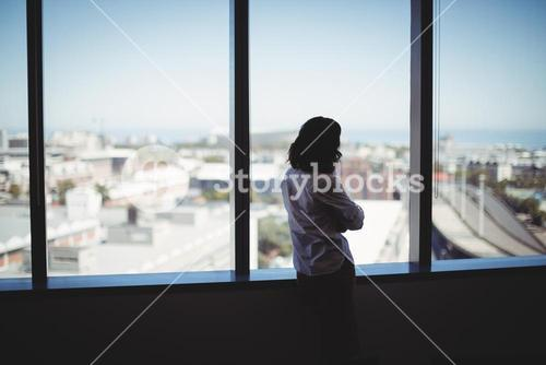 Female executive looking through window