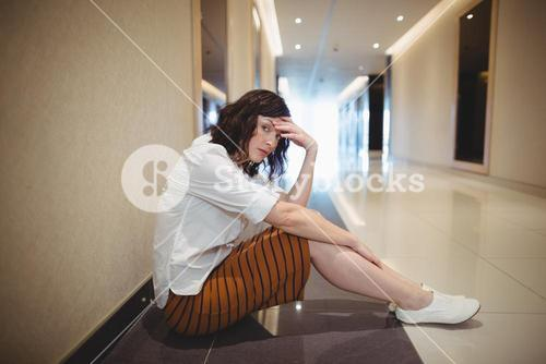 Portrait of sad female executive sitting in corridor