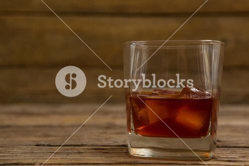 Glass of whisky with ice cube
