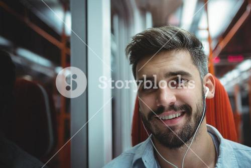 Executive listening music while travelling in train