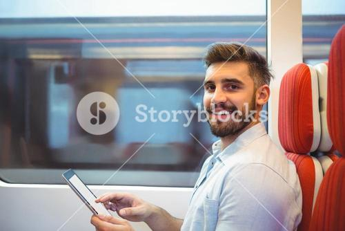 Executive using digital tablet travelling in train