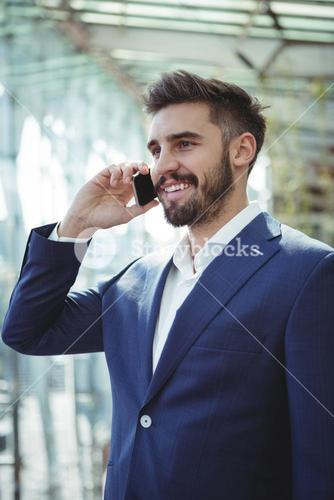 Businessman talking on mobile phone at railway station