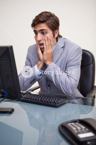Businessman getting negative surprised by his computer
