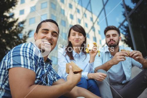 Smiling executives having breakfast outside office building