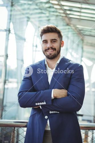Businessman standing with arms crossed at railway station