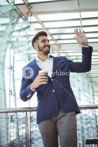 Businessman waving hand while having coffee at railway station