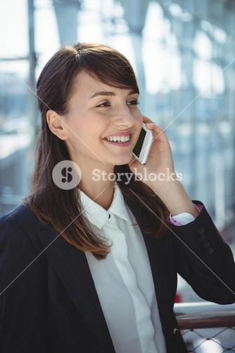 Businesswoman talking on mobile phone at railway station