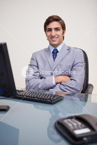 Businessman with folded arms leaning back satisfied