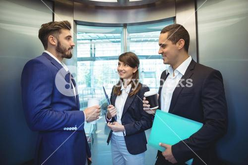 Business executives interacting in lift