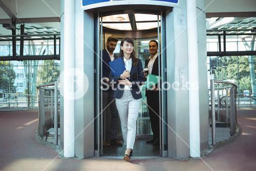 Business executives coming out from lift