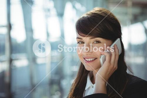 Smiling businesswoman talking on mobile phone at railway station