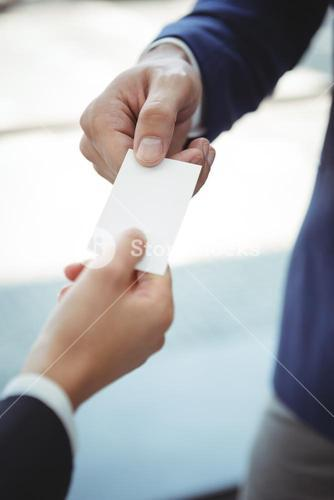 Businesswoman giving visiting card to businessman on platform