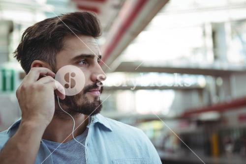 Thoughtful executive listening to music on headphones