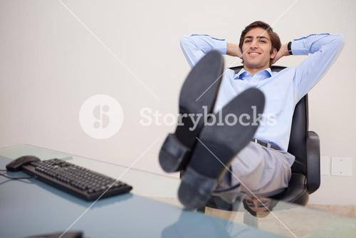 Smiling businessman leaning back in his chair
