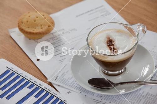 Coffee cup with spoon and documents
