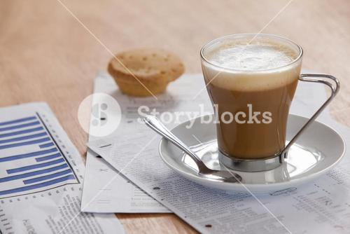 Coffee cup with saucer, spoon and documents