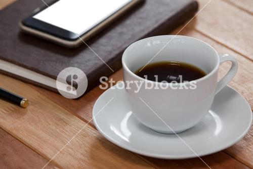 Black coffee with organizer and mobile phone