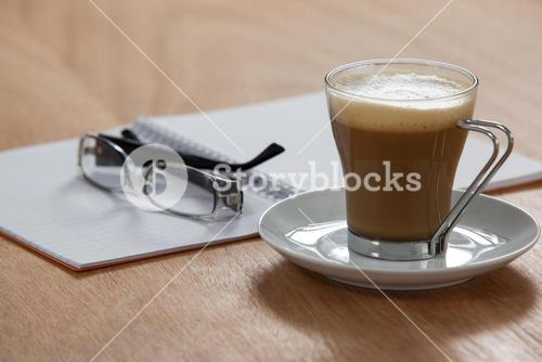 Cup of coffee with spectacles and organizer