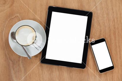 Cup of coffee with digital table and mobile phone