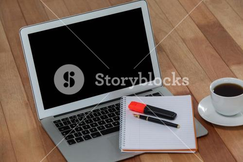 Cup of coffee with laptop, organizer, maker and pen