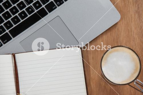 Cup of coffee with laptop and organizer