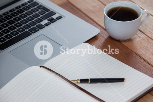 Cup of coffee with laptop, organizer and pen