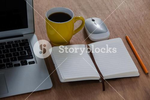Cup of coffee with laptop, organizer, pencil and mouse