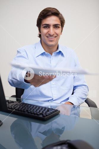 Smiling businessman handing over paperwork