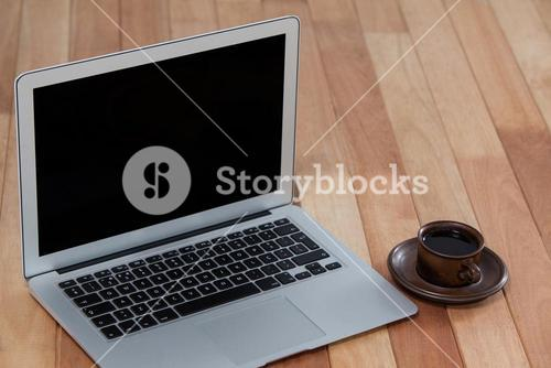 Cup of black coffee and laptop