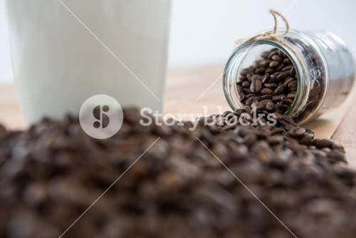 Close-up of coffee beans spilling out of jar