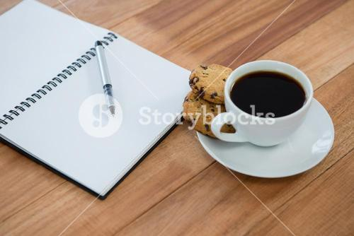 Open diary with pen and black coffee