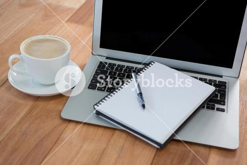 Cup of coffee with organizer and laptop