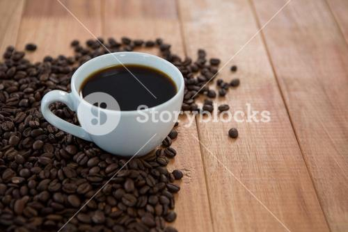 Cup of black coffee with roasted coffee beans