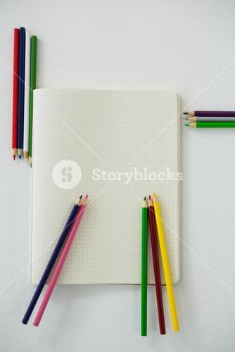 Colored pencils with book
