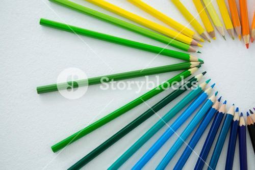 Colored pencils arranged in semi circle on white background