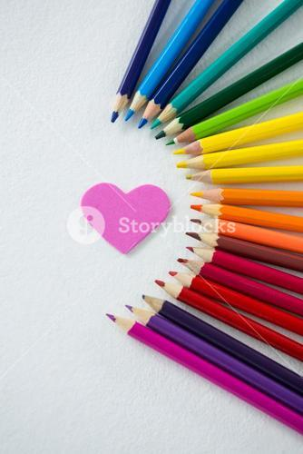 Colored pencils arranged in semi circle with heart on white background