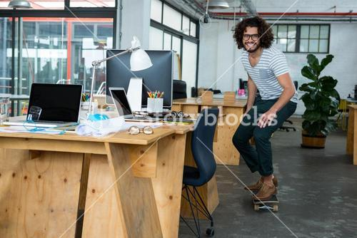 Graphic designer skating with skateboard in creative office