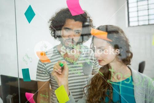 Executives writing on sticky notes