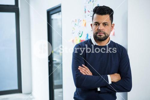 Graphic designer standing with hands crossed in creative office