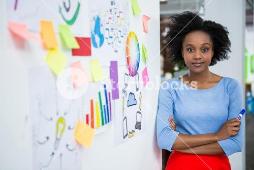 Female graphic designer standing with hands crossed in creative office