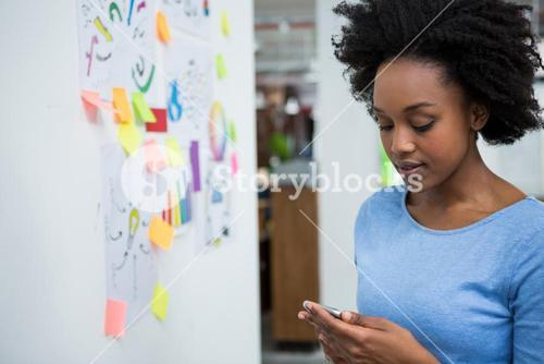 Female graphic designer using mobile phone