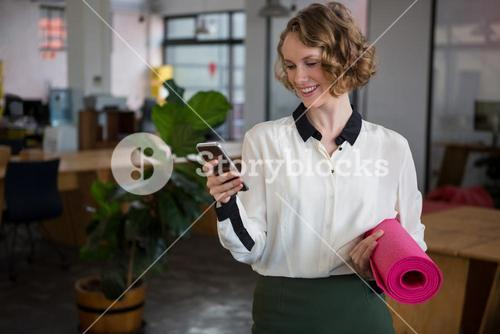 Female graphic designer using mobile phone while holding yoga mat