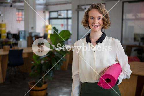 Female graphic designer holding yoga mat